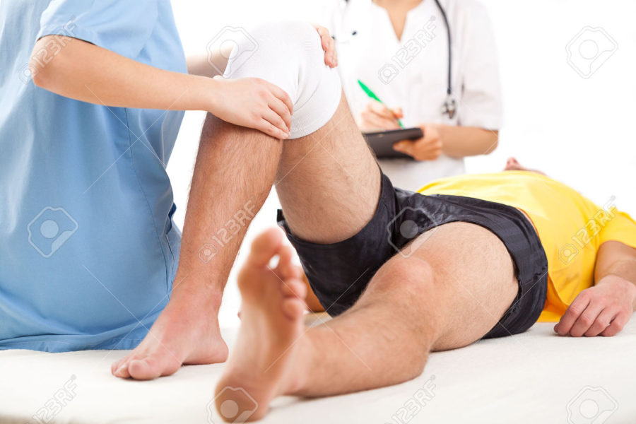 24495773-Qualified-medical-team-examining-knee-condition-in-clinic-for--Stock-Photo